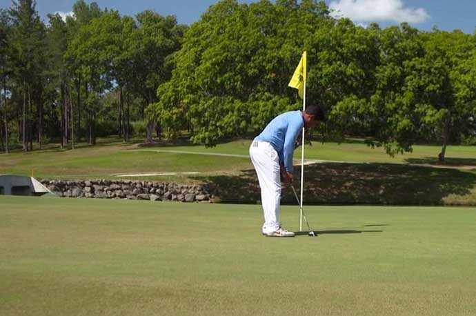 Golfer putting with flagstick in