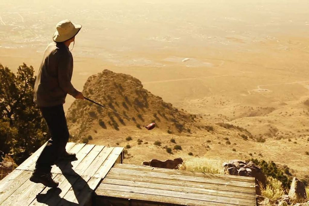 Golfer stands on platform on top of Socorro's M Mountain ready to hit shot in the Elfego Golf Shoot.