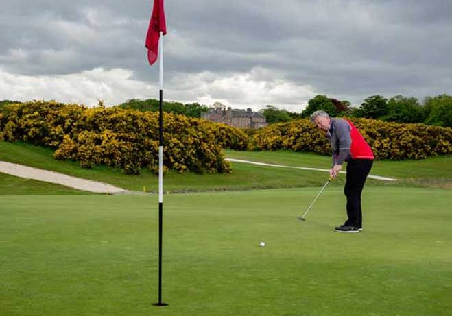 Man putting with flagstick in